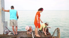 Stock Video Footage of Family of four people fish together on a concrete pier
