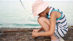 Girl opens a shell on the concrete pier near the sea Stock Footage