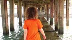 A woman walks under the concrete structure in the sea Stock Footage