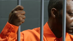 Black male inmate in jail cell, eyes down, dolly shot Stock Footage