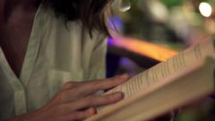 Young woman reading book at night Stock Footage
