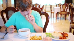 Boy eats soup in a restaurant and shows the number two with hand Stock Footage