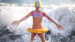 Girl in inflatable ring and a rubber cap in the sea waves - stock footage