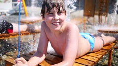 The boy lies on a lounger with running water on beach Stock Footage