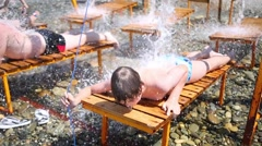 The boy lies on a lounger under running water Stock Footage
