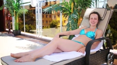 Woman rests in the shade on a sun lounger at the resort Stock Footage