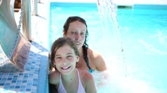 Mother and daughter stands in water under a waterfall Stock Footage