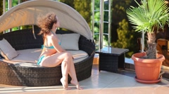 A woman in a swimsuit sits on a sofa with a canopy at the resort Stock Footage
