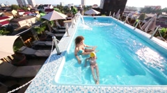 Mother and daughter in the rooftop pool in Shine House Hotel Stock Footage