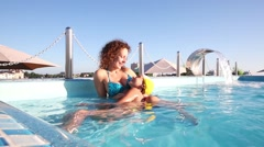 Mother and daughter in the rooftop pool at the evening Stock Footage