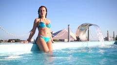 A woman is leaning on the edge of the rooftop pool in the evening Stock Footage