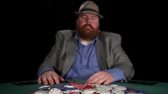 Poker player plays with chips in the pot as he drags them toward him and laughs - stock footage