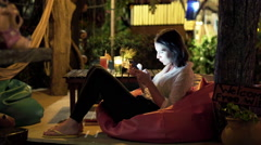 Young woman using smartphone and drinking cocktail in cafe at night Stock Footage