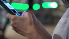 Woman hands texting on smartphone and drinking cocktail at night - stock footage