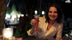 Young, happy woman raising toast to camera and drinking cocktail in cafe at nigh Stock Footage