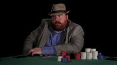 Poker player appears agitated as he awaits his turn to make a bet Stock Footage