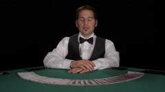 Dealer picks up a deck of cards fanned out in front of him and then smiles - stock footage