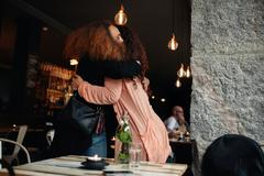 Two young women meeting at a restaurant Kuvituskuvat