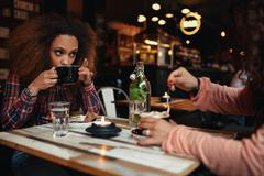Young woman drinking coffee at cafe Stock Photos