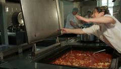 Cook closing vessel with macaroni, other cooks preparing cheese pies in kitchen. Stock Footage