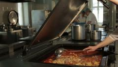 Cook stirring macaroni with ladle and other cooks preparing pies in the kitchen. Stock Footage