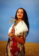 Young woman with ornamental dress and white fur standing on a wheat field with - stock photo