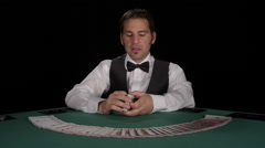 Dealer shuffles a deck of cards with another deck fanned out and then smiles - stock footage