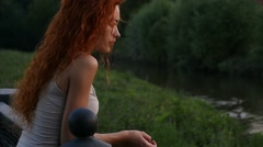 Pretty upset sad red haired unhappy girl standing by river alone, slow motion. Stock Footage
