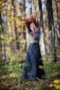 Red haired woman dancing in autumn forrest Stock Photos