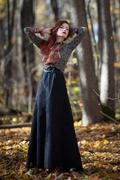 Stock Photo of Red haired woman dancing in autumn forrest