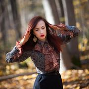 Red haired woman dancing in autumn forrest - stock photo