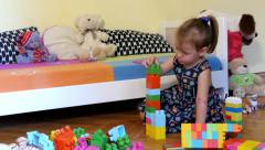 Beautiful female kid playing with colorful dices in bedroom. Leisure time. - stock footage