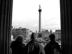 Tourists admiring Trafalgar Square in London - stock photo