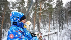 Pregnant smiling woman rides a lift up the mountain in a ski suit - stock footage