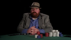 Poker player looks at cards and counts his chips as he deliberates making a bet - stock footage