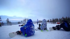 Russia. Siberia. 27 december 2014. Tourists snowboarders prepare for playing ski Stock Footage