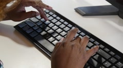 Close up of the hands of a african woman with a computer keyboard Stock Footage