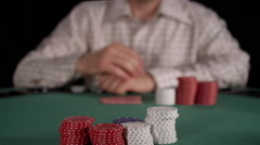 Focus shifts from chips in pot to poker player who looks at cards and places bet - stock footage