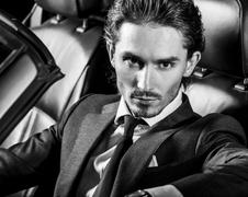 Handsome man with beard in suit driving car - stock photo
