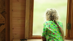 Girl look out the window - view from the back Stock Footage