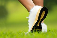 human feet in running shoes to step on the grass - stock photo