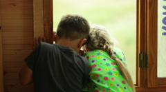 boy and girl look out the window - view from the back - stock footage