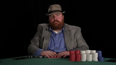 Poker player receives two cards, looks at them, and then places a bet - stock footage