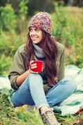 smiling young woman with cup sitting in camping - stock photo