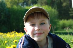 Smiling boy with blue eyes looking at camera - stock photo