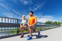 smiling couple stretching outdoors - stock photo