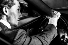 Handsome man with beard in suit driving car Stock Photos