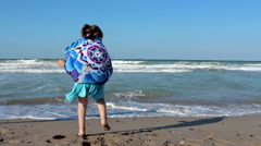 Little girl in blue dress enjoying on seashore, Slow Motion Stock Footage