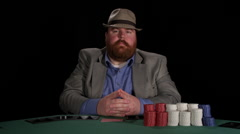 Poker player looks at his cards and then places a bet - stock footage