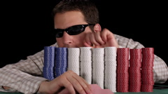 Poker player counts his large stacks of chips that partially hide him Stock Footage